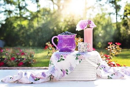purple ceramic pitcher on white wicker picnic basket during daytime