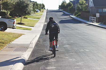 man wearing black backpack riding on red bike on road during daytime