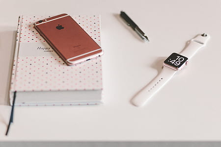 Silver Apple Watch White Sports Band Near Rose Gold Iphone 6 on White Wooden Table