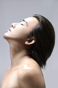 man closing eyes facing upward