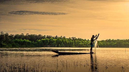 man on boat holding fish net