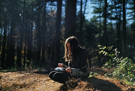 woman sitting on brown grass holding book