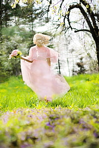woman in pink chiffon dress holding pink of flower bouquet running at daytime