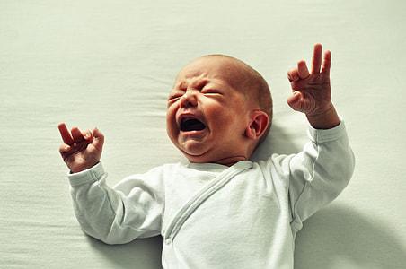 baby wearing white long-sleeved shirt crying