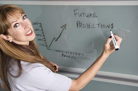 woman writing on white board using black marker