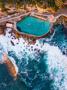 aerial photography of pool beside cliff