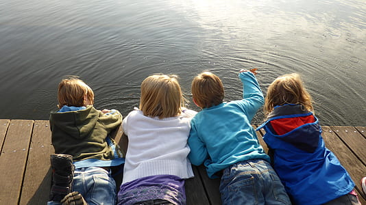 four children lying on brown deck while staring at body of water