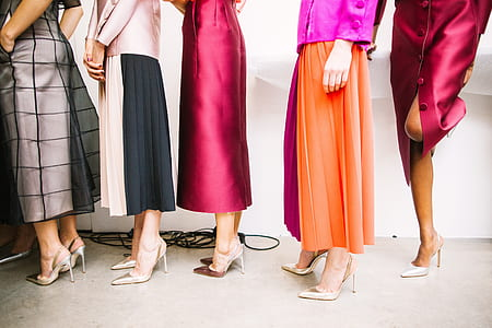 five women wearing assorted-color dresses and heeled shoes while standing near white wall