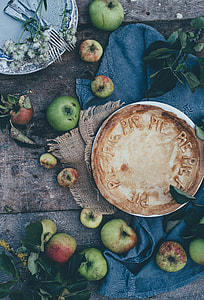 round baked pie surrounded with green apples