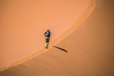 man walking in desert during daytime