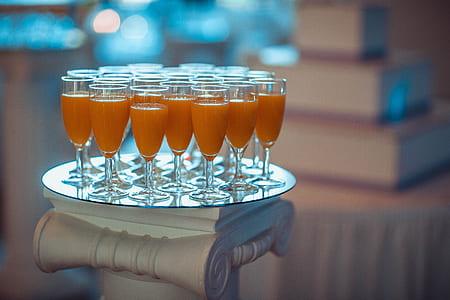 cocktail glasses filled with orange liquid content