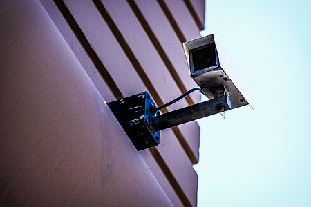 worm's eye view photography of white CCTV camera mounted on brown building during daytime