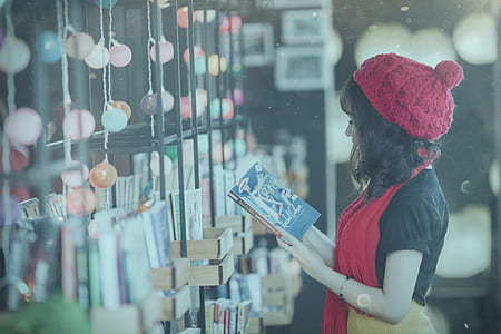 woman in red hat reading book during daytime