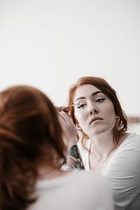 woman putting liquid eyeliner photograph