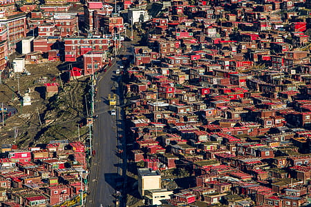 aerial view of red painted building and houses with main concrete road