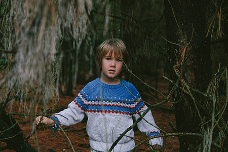 boy wearing teal, white and red sweater
