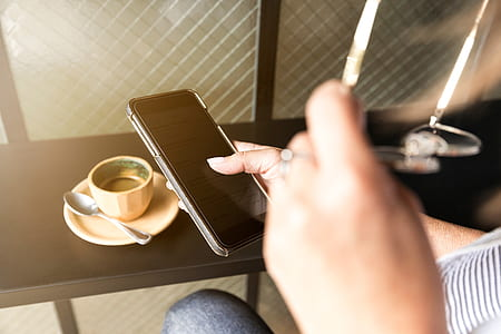person holding smartphone near brown coffee cup with spoon