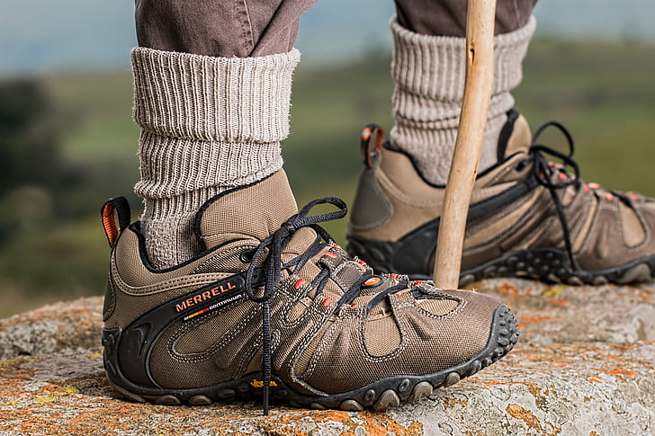 Men's Brown and Gray Merrell Hiking Shoes Holding Stick