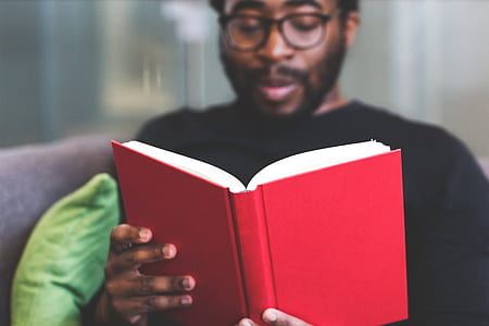 man in black crew-neck shirt reading red book