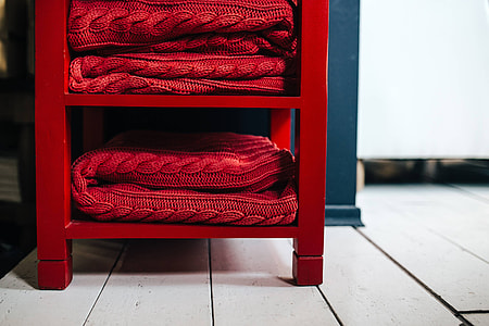 Folded sweaters and fabrics stacked on shelves