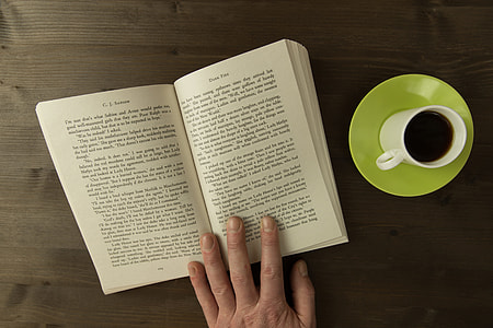 Overhead shot of a man reading a book with a cup of coffee on desk