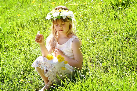 girl wearing white lace dress and flower crown sitting on green grass