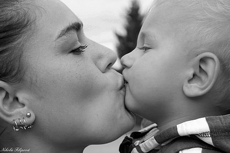 photo of woman kissing her son