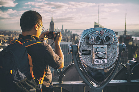 A tourist takes a picture with his camera on the Top Of The Rock observation deck at the famous Rockefeller Center, Manhattan, New York City