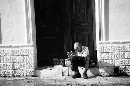 grayscale photo of man sitting on entrance displaying books