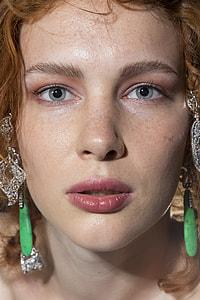 close view of woman wearing green gem earrings