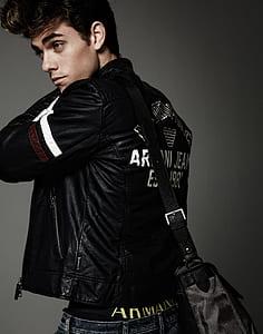 man wearing black leather jacket and bag