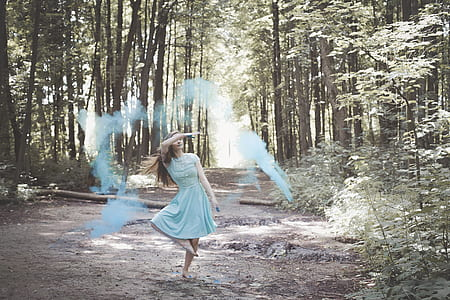 woman in blue dress with blue color powder during daytime