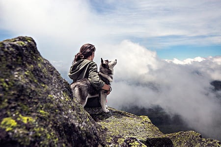 person holding husky sitting on mountain near clouds