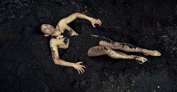 man covered in black soil