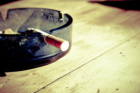 single cigarette on glass ashtray