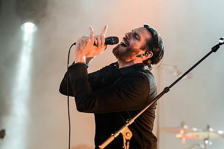 Man Wearing Black Collared Long Sleeve Shirt Holding Microphone