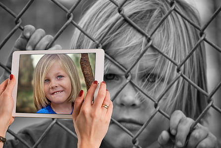 grayscale photograph of boy holding on chain link fence