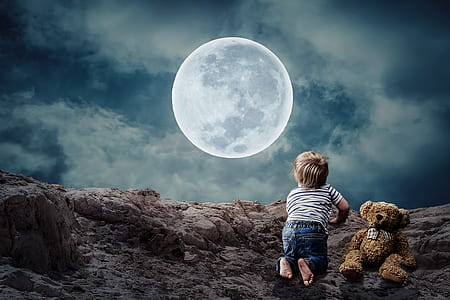 boy beside bear plush looking at moon