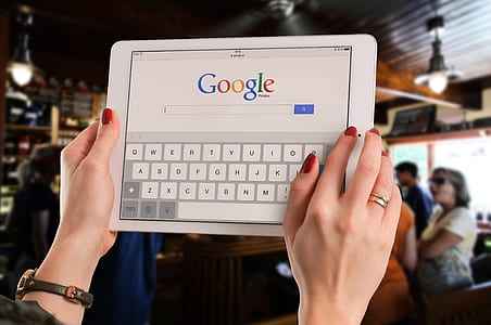 person using iPad searing in google search engine