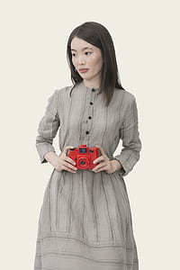 woman in gray dress holding red camera