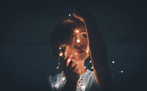 woman wearing white lace top holding string of lights photography