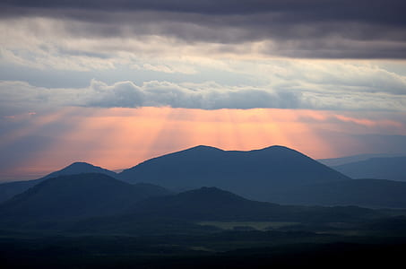 silhouette of mountain with ray of lights