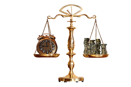brass-colored balance scale with analog clock and coins