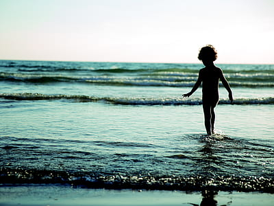 toddler walking on body of water