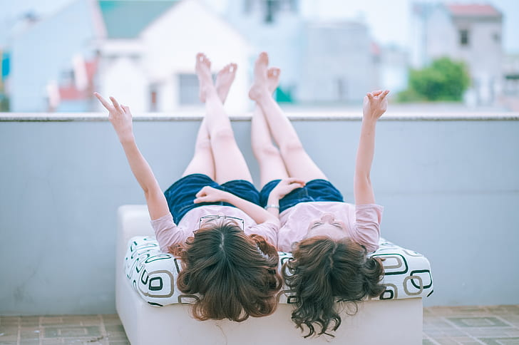 two girl's wearing same shirts and shorts lying down on roof top