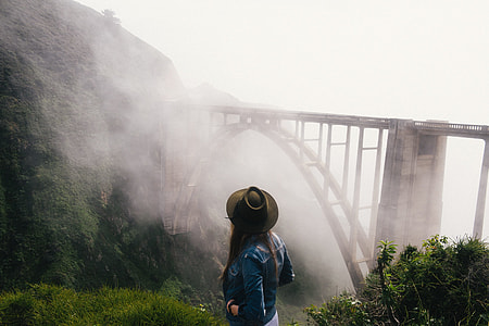 woman in cowboy hat and blue denim jacket standing on cliff with a view of concrete train bridge covered with fogs
