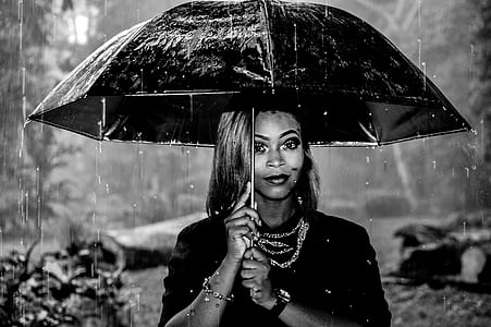 grayscale shallow focus photography of woman holding umbrella under rain