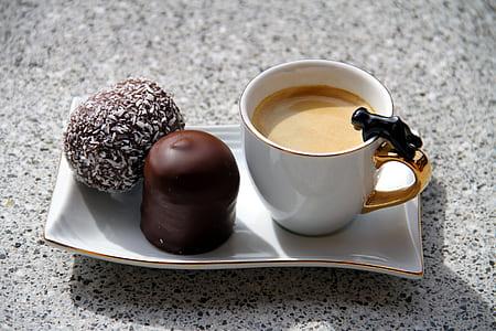 liquid filled ceramic mug beside cakes on tray