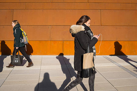 Street shot of a young woman using her mobile iPhone smartphone in Vienna, Austria