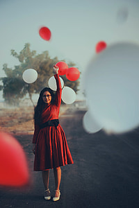 woman in red long-sleeved midi dress holding balloon during daytime